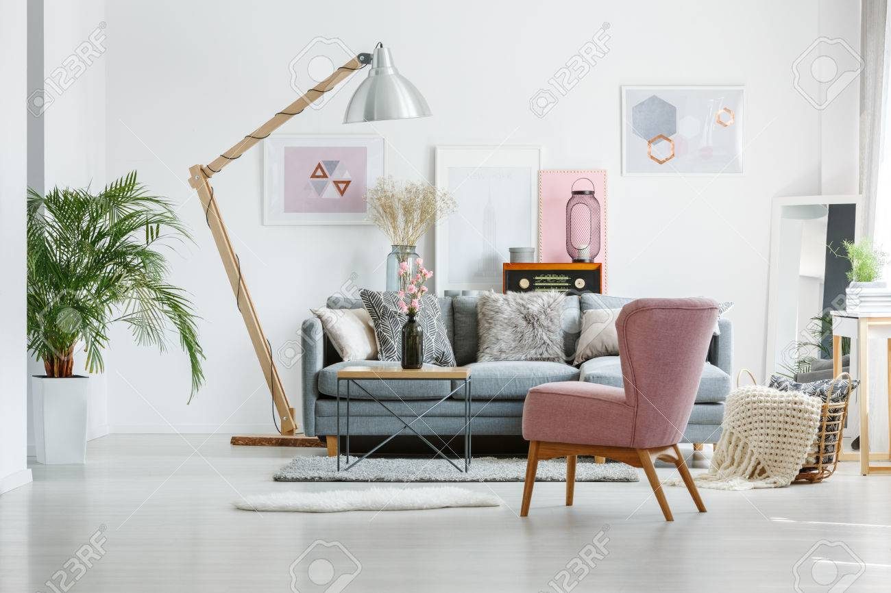 living room arm chair colors with grey walls beige blanket in basket on floor pink armchair and artistic posters