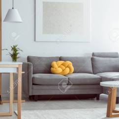 Grey Sofa Living Room Carpet Corner Furniture Yellow Knot Pillow On In Cozy With White Stock Photo Floor And Simple Painting Wall