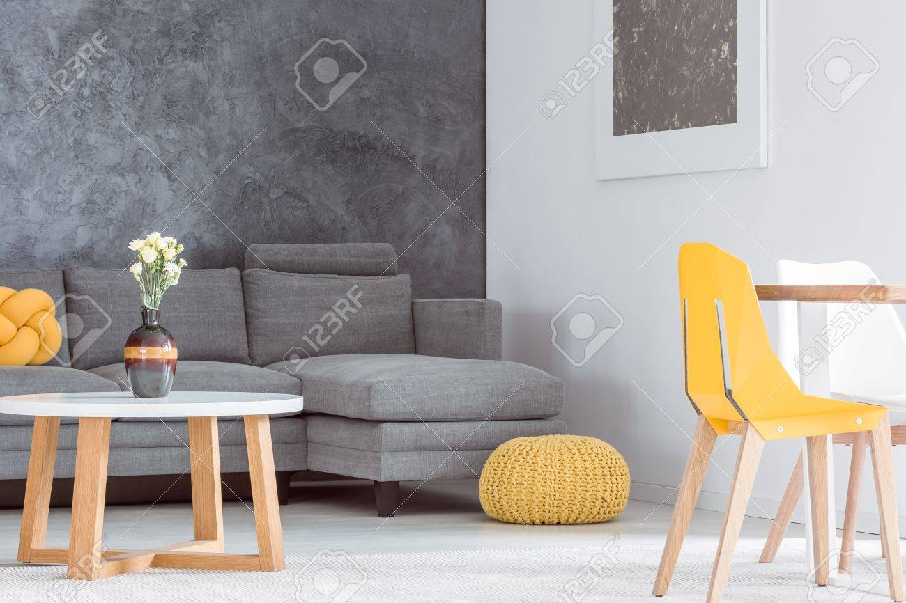 https www 123rf com photo 84779093 decorative vase with flowers on wooden coffee table in living room with grey sofa and yellow equipme html