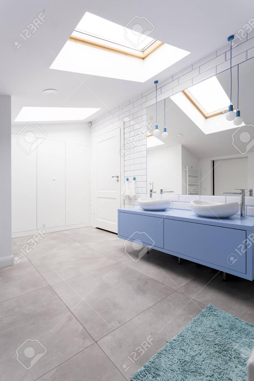 confortable salle de bain mansardee avec sol gris meuble vasque bleu miroir et fenetre banque d images et photos libres de droits image 84779219