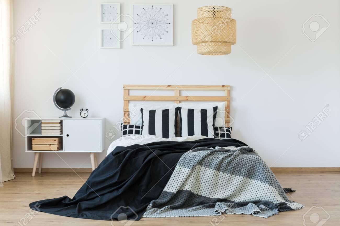 lit avec tete de lit en bois dans la chambre noire et blanche banque d images et photos libres de droits image 85134196