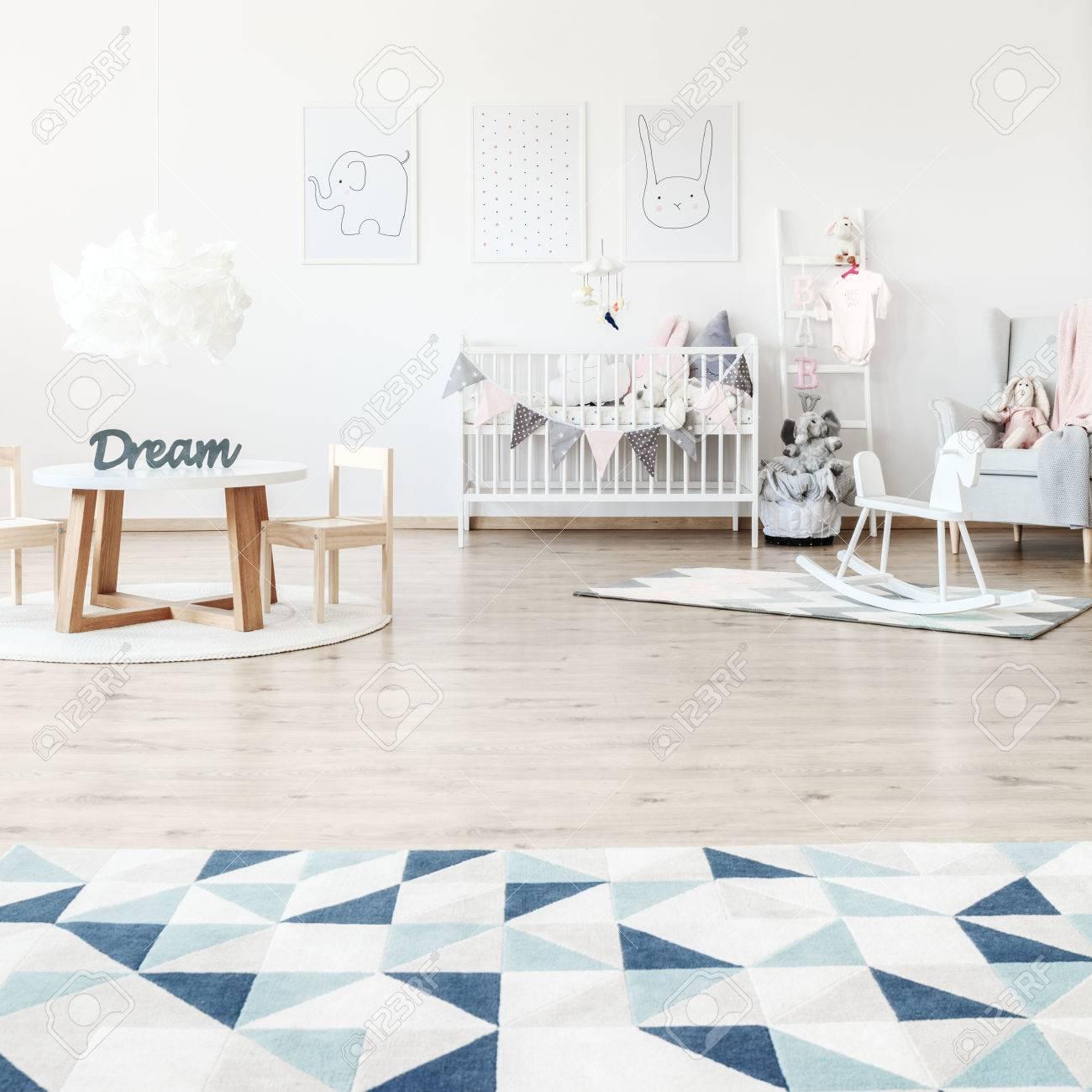 tapis triangle dans la chambre d enfant spacieuse avec cheval a bascule petite table et lit blanc banque d images et photos libres de droits image 87171283