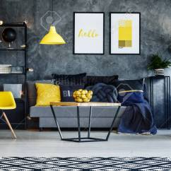 Yellow And Grey Chair Couch Rocking Chairs In Dark Living Room With Poster On Concrete Wall Stock Photo Lamp Above Sofa