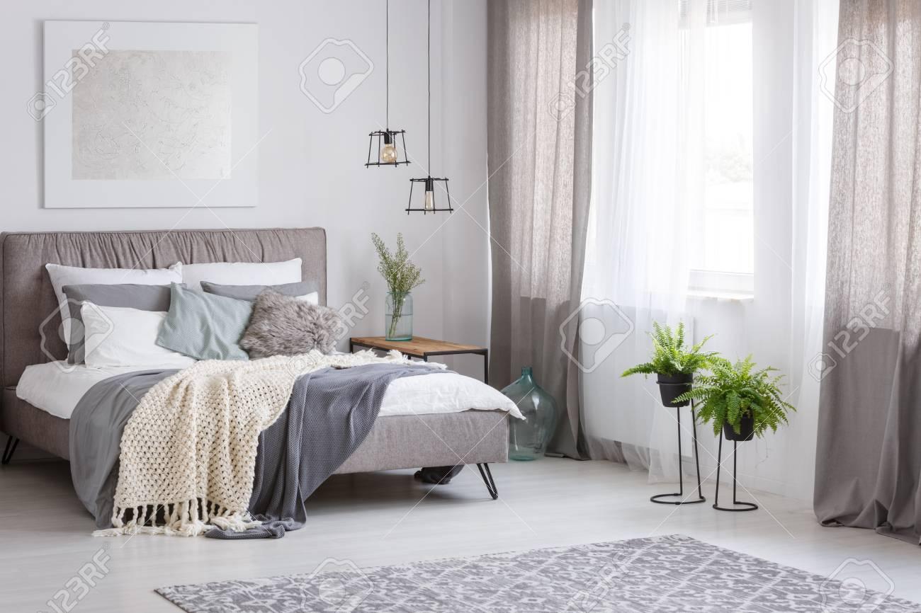 banque d images une literie grise et un oreiller a la menthe sur un lit king size dans une chambre sophistiquee aux couleurs douces avec des fougeres