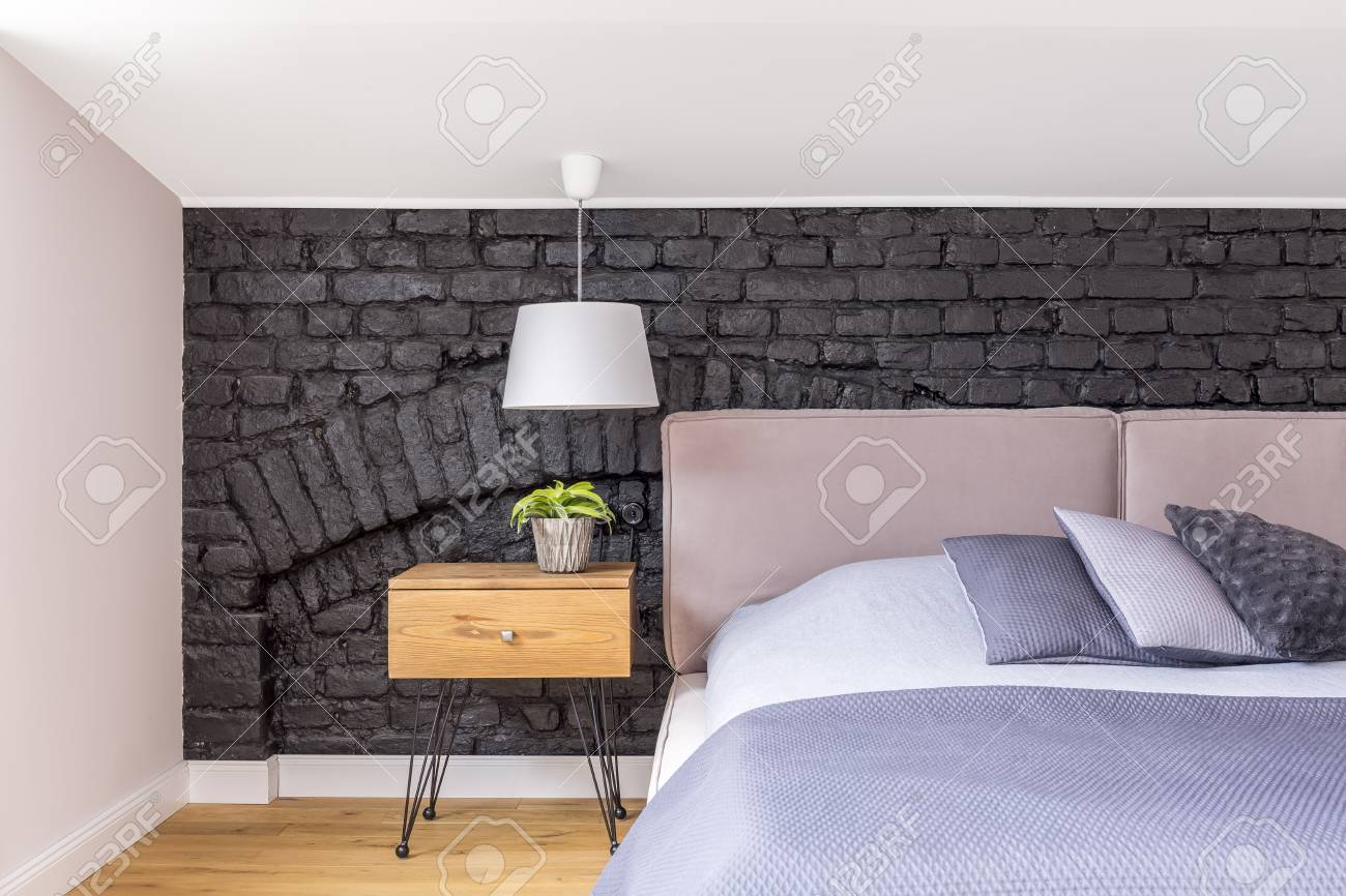 https www 123rf com photo 88394528 bedroom with wooden bedside cabinet with plant next to king size bed against black brick wall html