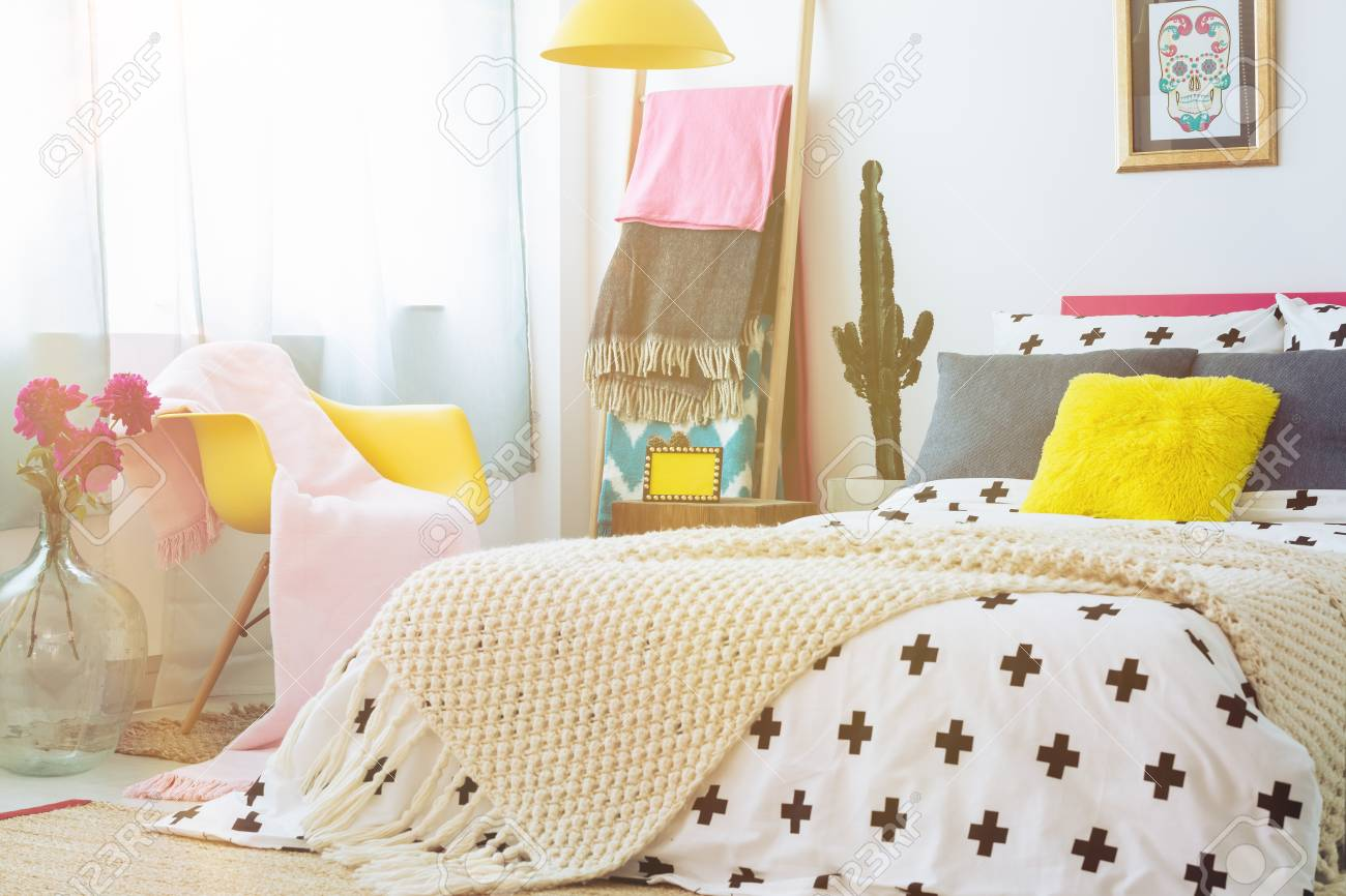 bedroom chair with blanket car seat office yellow pink next to king size bed stock photo pillow and beige in mexican cactus