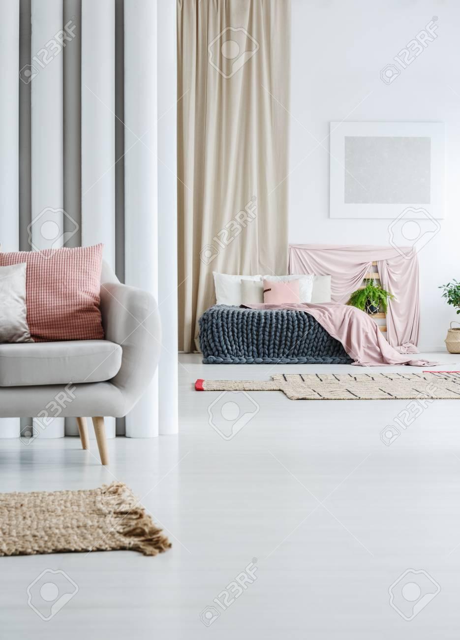 rideau beige dans loft multifonctionnel avec canape gris et couvre lit rose sur lit king size banque d images et photos libres de droits image 89879071