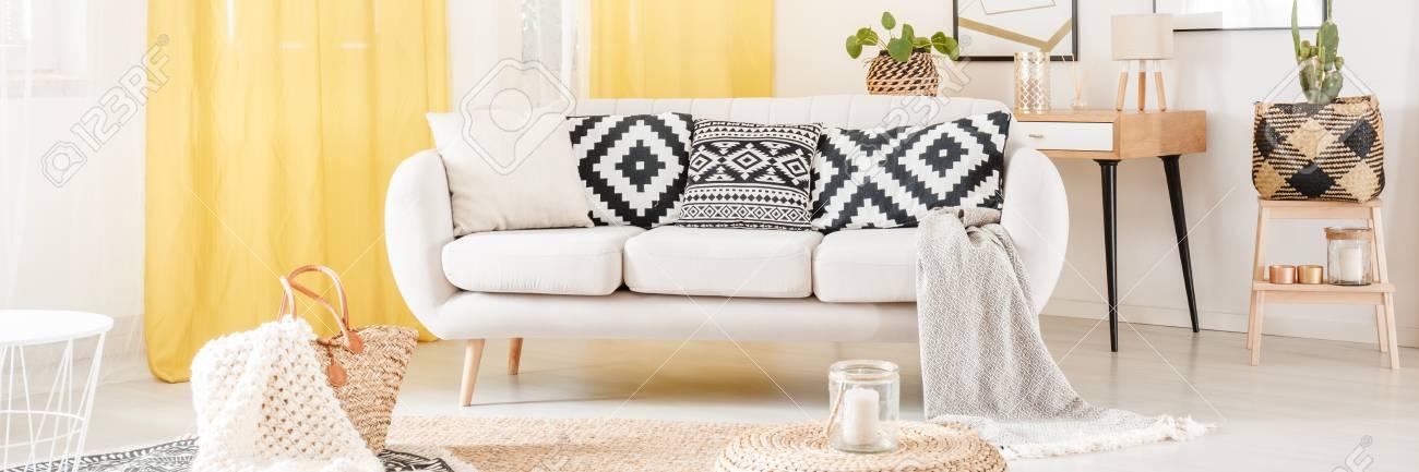 coussins a motifs noir et blanc sur canape en style scandinave salon avec rideaux jaunes banque d images et photos libres de droits image 97991457