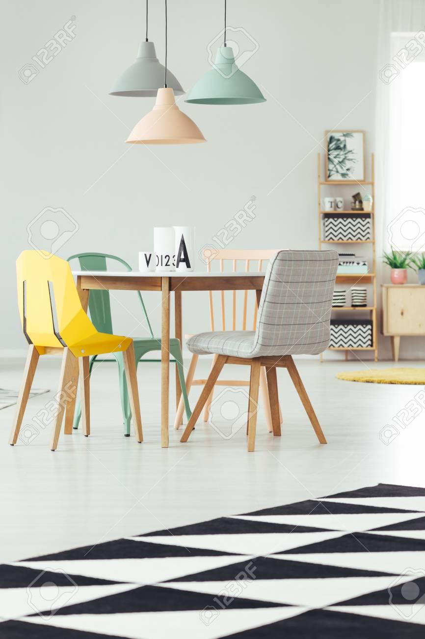 tapis noir et blanc a l interieur d une salle a manger pastel avec chaises colorees a une table en bois sous une lampe menthe peche et gris banque d images et photos libres de