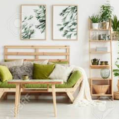 Green Cushions Living Room Decorating Ideas With Black Leather Couch Wooden Table In Front Of Floral Stock Photo Interior Leaves Posters And Suitcase On Shelf