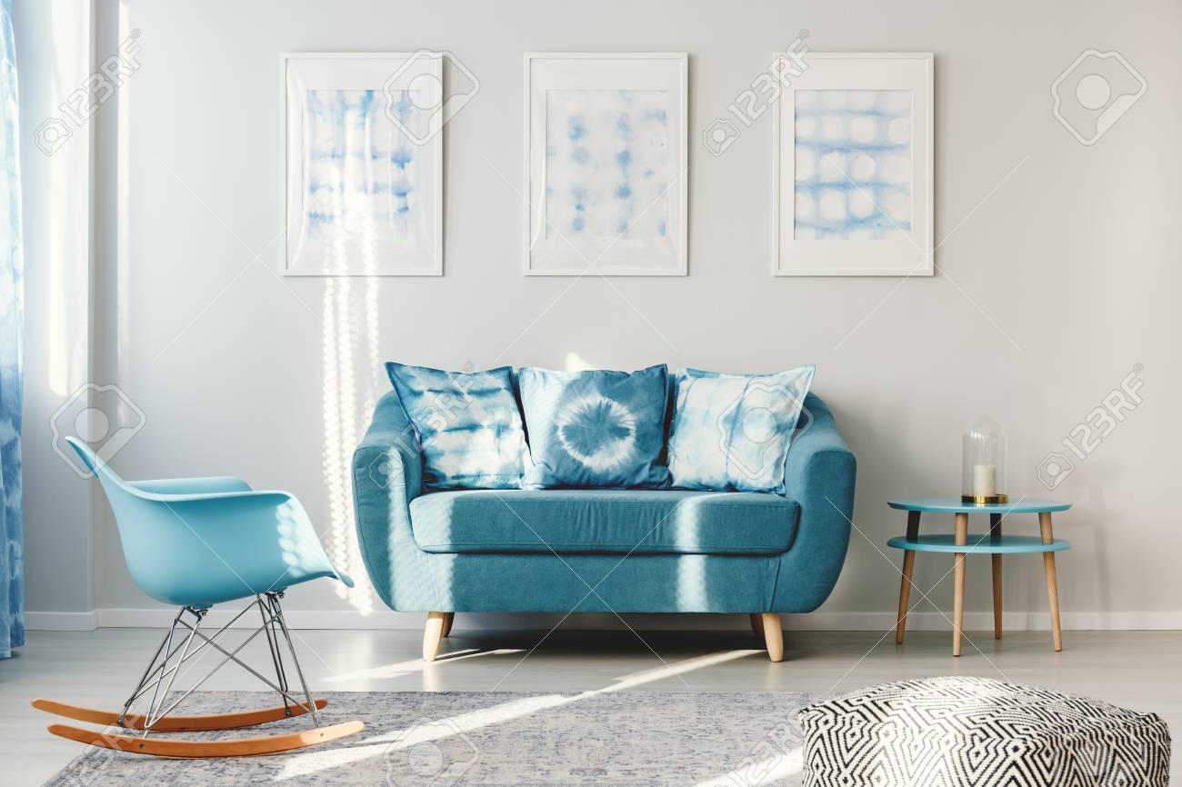sofa rocking chair modular ikea turquoise with pillows between round table and blue stock photo in living room interior posters