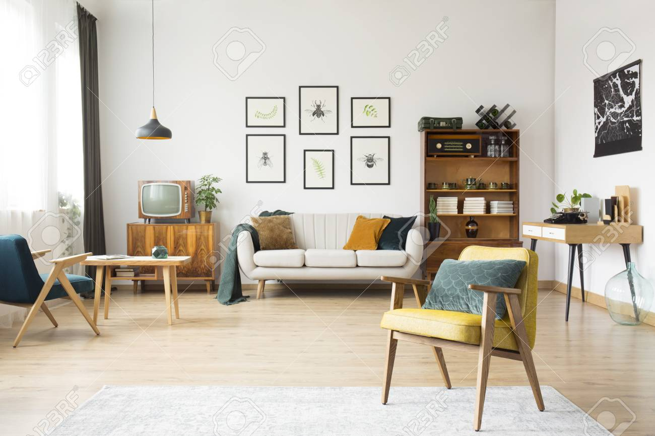 retro living room buffet for interior with beige sofa against white wall posters and black lamp above