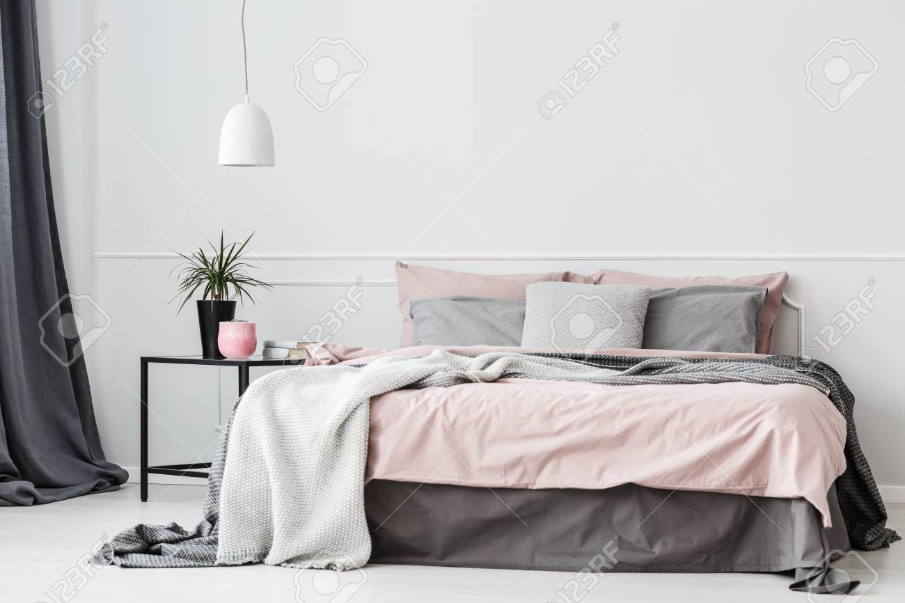 Grey And Pink Bedsheets On Bed Next To Nightstand With Plant