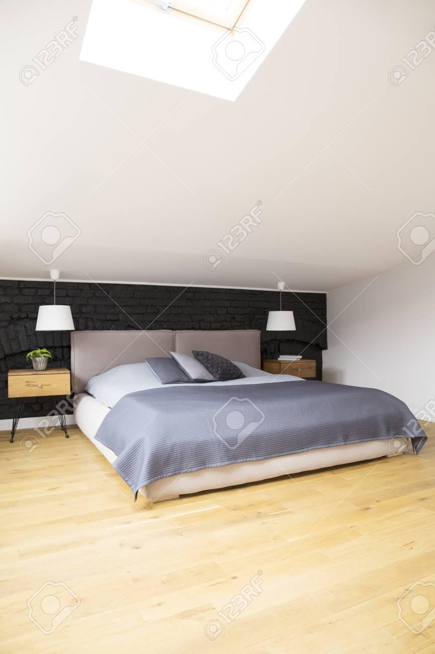 Grey Bed Between Wooden Nightstands And White Lamps In Bedroom