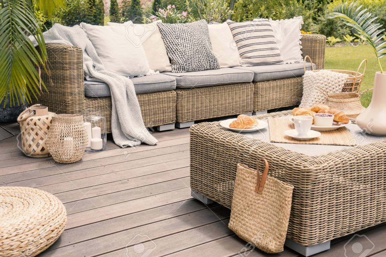 wicker patio set with beige cushions standing on a wooden board stock photo picture and royalty free image image 107758880