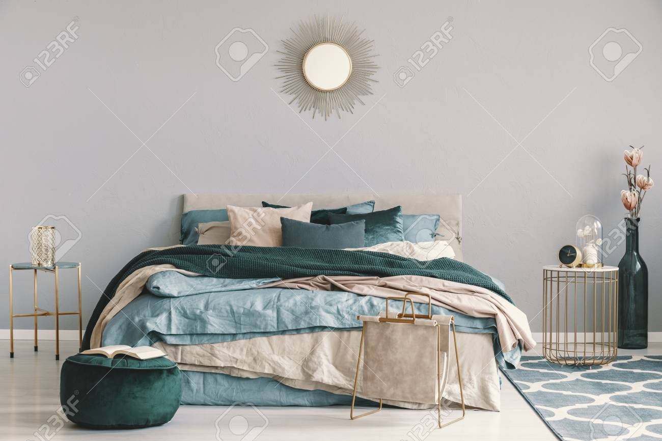blue beige and emerald green bedding on king size bed in contemporary