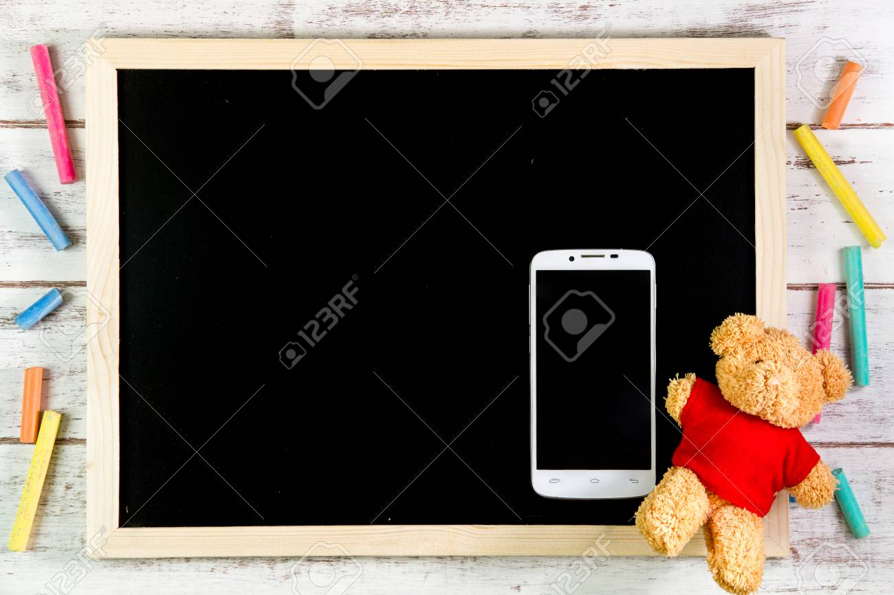 Blank Blackboard, Teddy Bear And Smart Phone On Wooden Table.template Mock  Up For