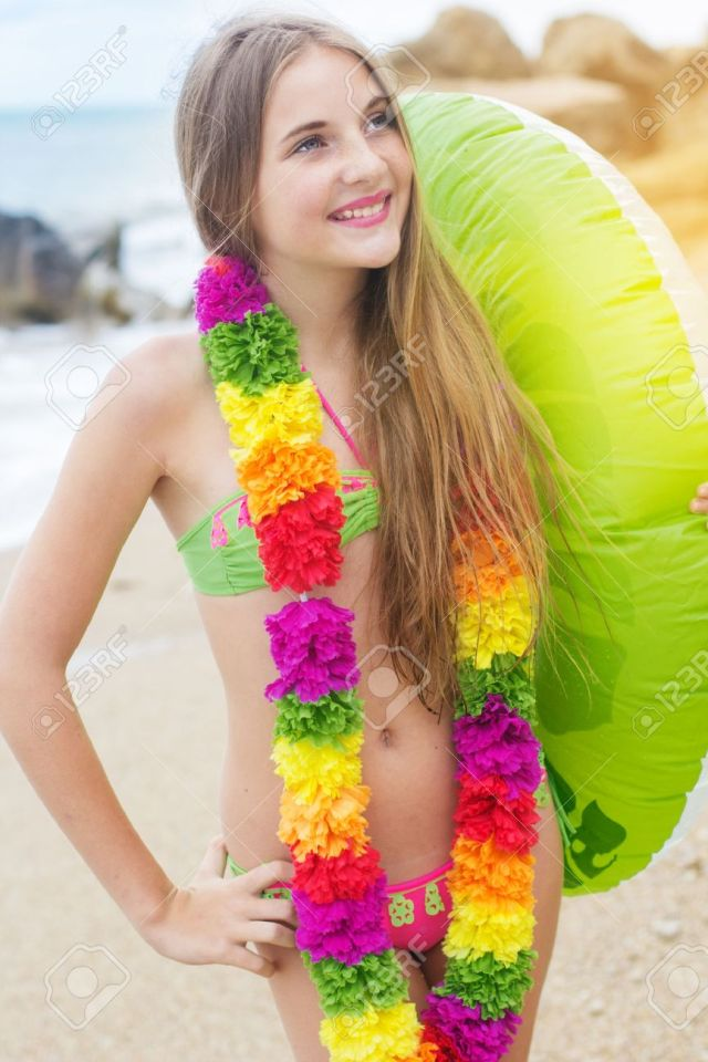 Cute Teen Girl Is Wearing Swimsuit And Hawaiian Colorful Flowers Walking At Beach With Green Rubber