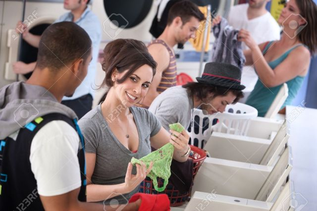 Stock Photo Woman Holds Panties And Flirts With Man In Laundromat