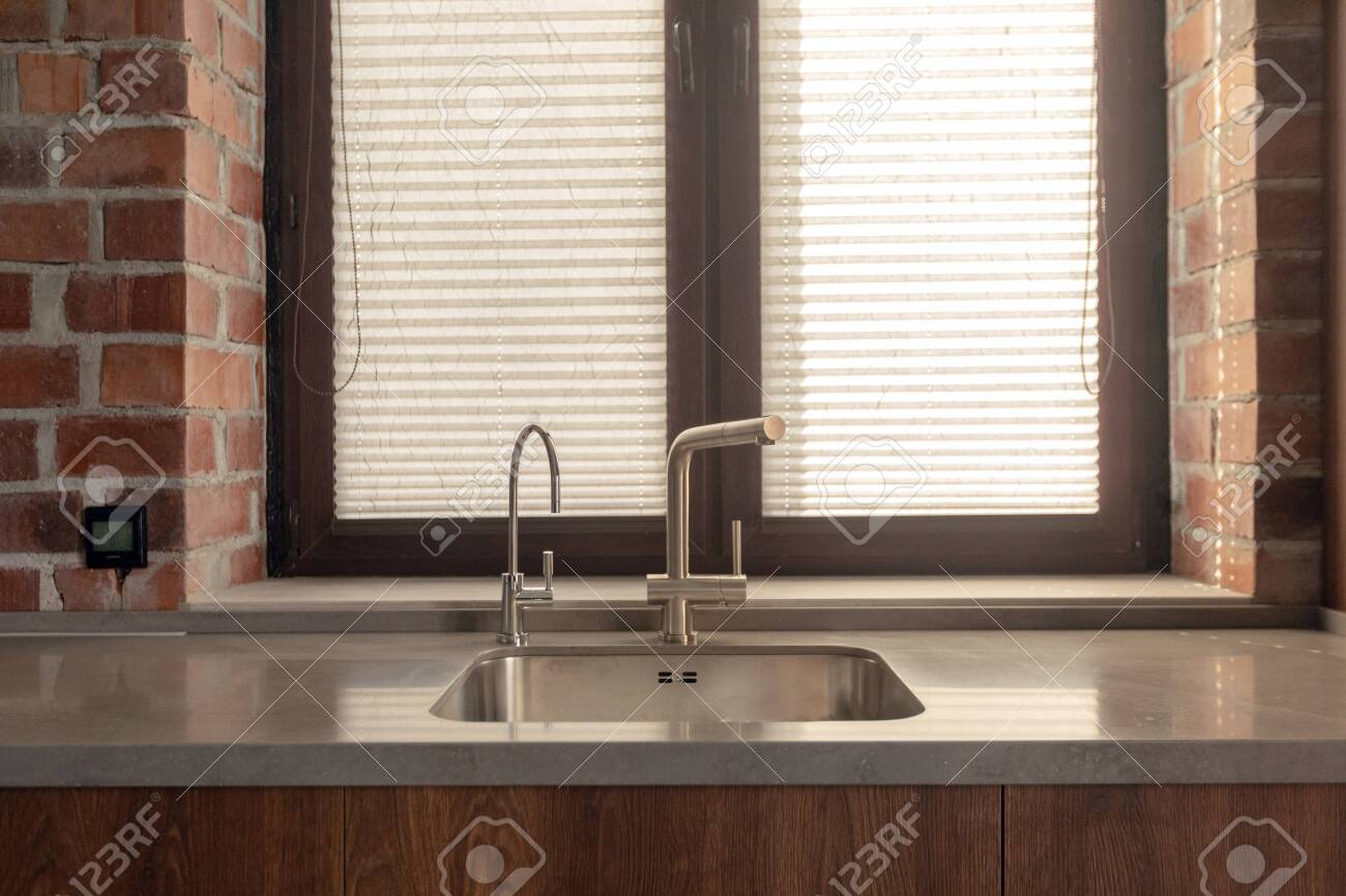 stainless kitchen sink with modern faucets against window with