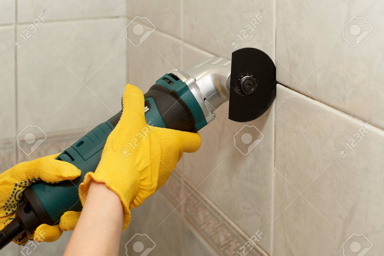 https www 123rf com photo 78023281 male hands with renovator multi tool removing the old grout replacing old grout between tiles raking html
