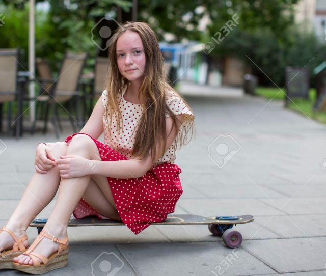 Cute Teen Girl Sitting On A Skateboard On The Street Stock Photo 42869412