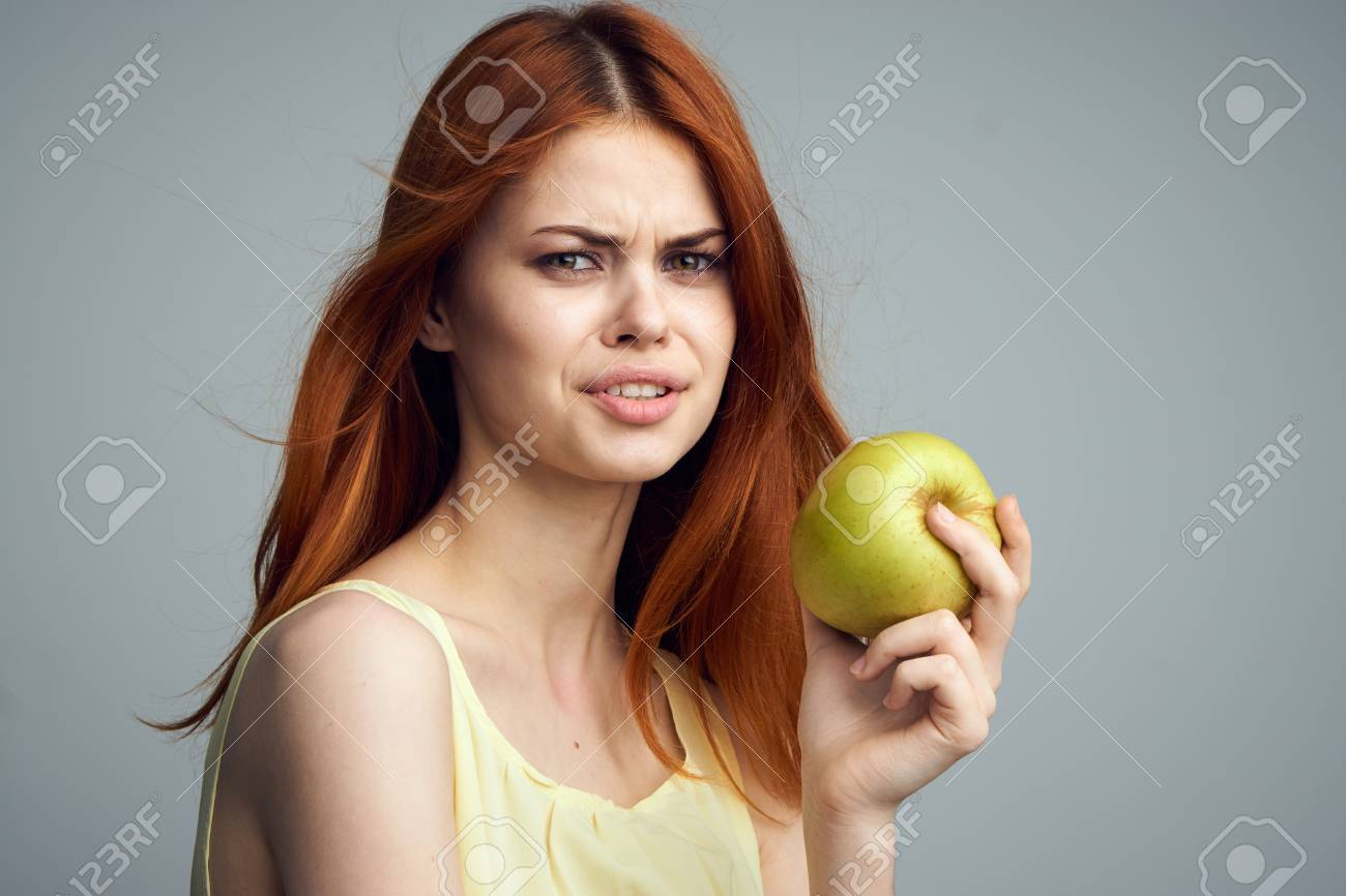 Woman With Red Hair On A Gray Background Holds An Apple Diet