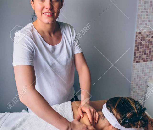 Portrait Of Smiling Female Massage Therapist Doing Relaxing Massage On Shoulders Of Young Woman In A