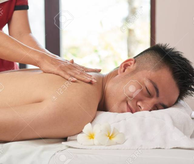 Handsome Asian Man With Closed Eyes Getting Back Massage While Lying On Treatment Table At Luxurious