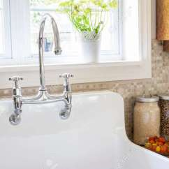 White Porcelain Kitchen Sink Air Gap Rustic With Curved Faucet And Tile Backsplash Under Large Window Stock Photo