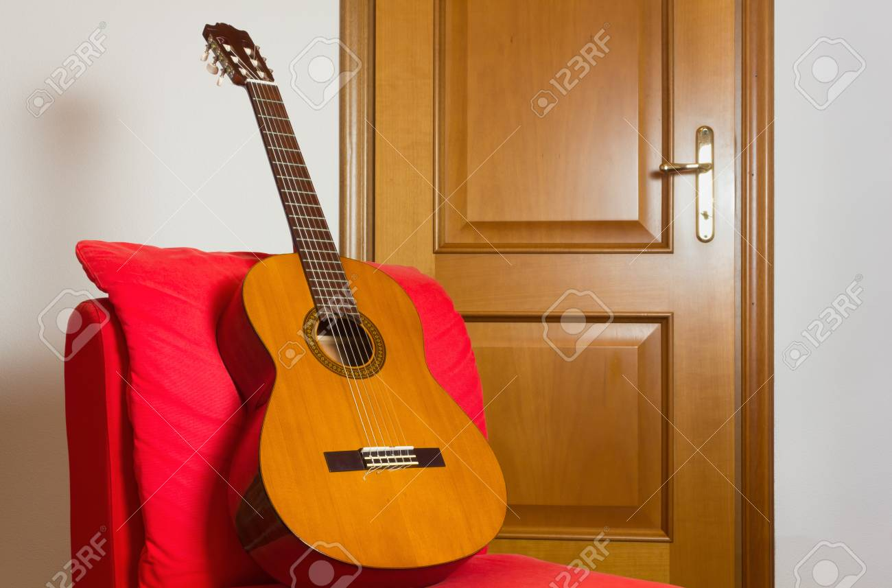 classical guitar chair parson covers ebay on a red easy with wooden door in the background stock photo