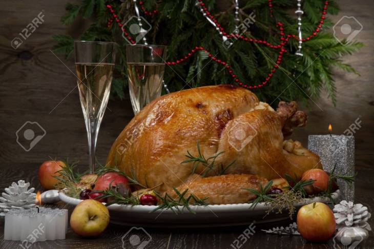 Garnished roasted Christmas turkey with grab apples, sweet chestnut,  cranberry, Christmas ornaments,