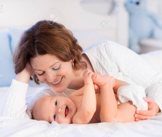 Mother And Child On A White Bed Mom And Baby Boy In Diaper Playing In