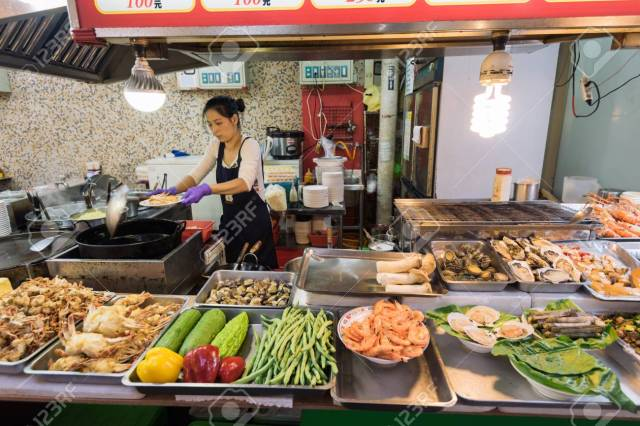 Taipei, Taiwan - April 6, 2017: Food stall at the The Shilin Night Market in Taipei, Taiwan. Shilin Night Market is a night market in the Shilin District of Taipei, Taiwan, and is often considered to be the largest and most famous night market in the cit - 83200329