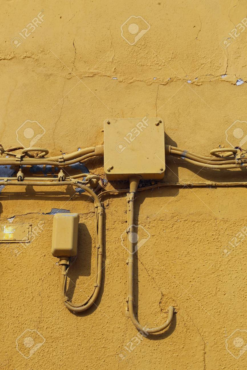 hight resolution of old yellow wall of the house and the junction box with the electric and telephone cables