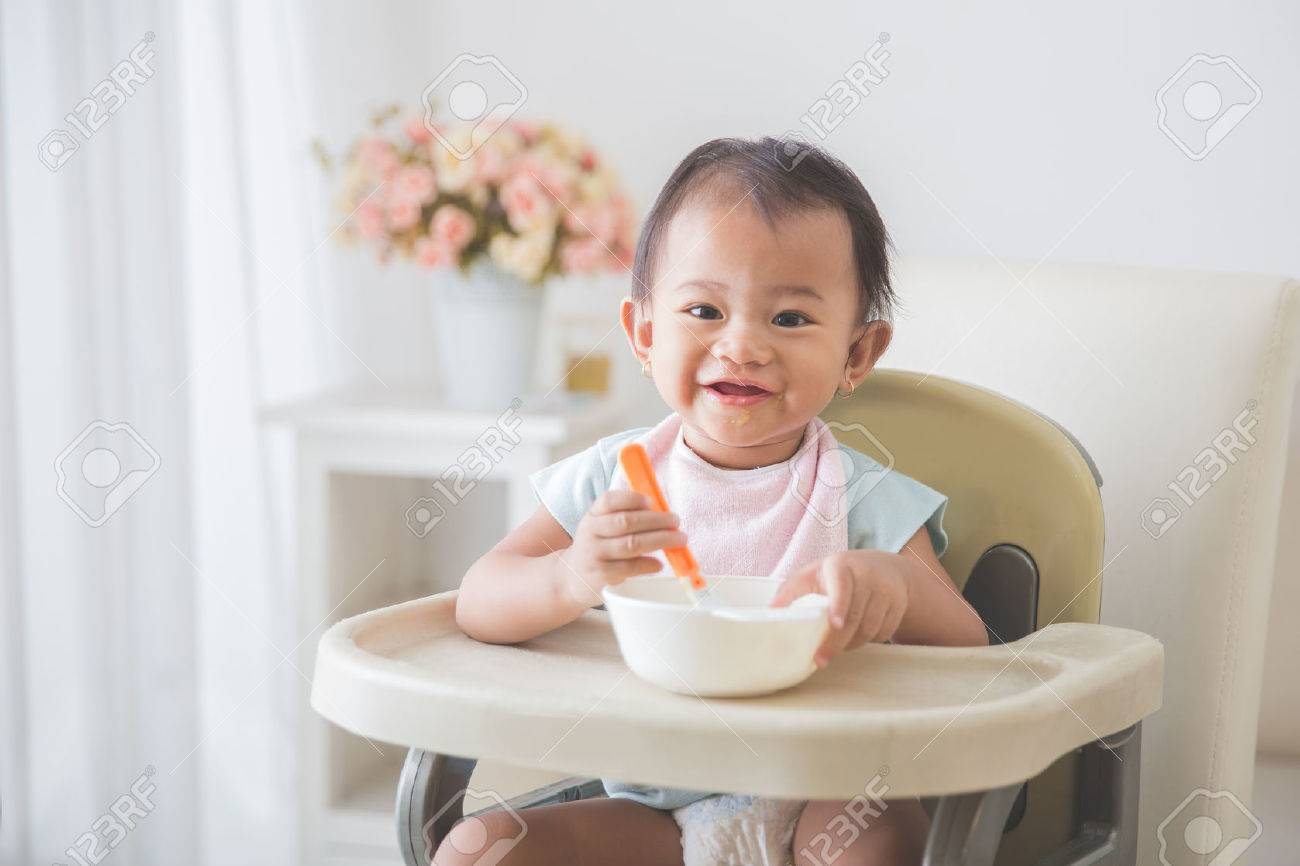 baby girl chair stool for toddlers portrait of happy young sitting on high and feed her self stock photo