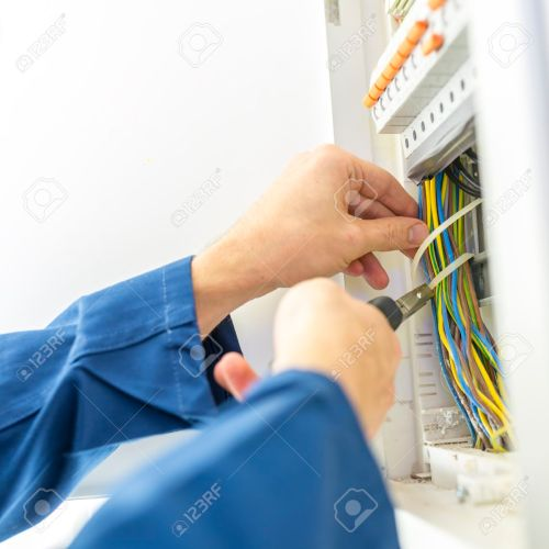 small resolution of electrician installing an electrical fuse box in a house working with pliers on the wiring circuits
