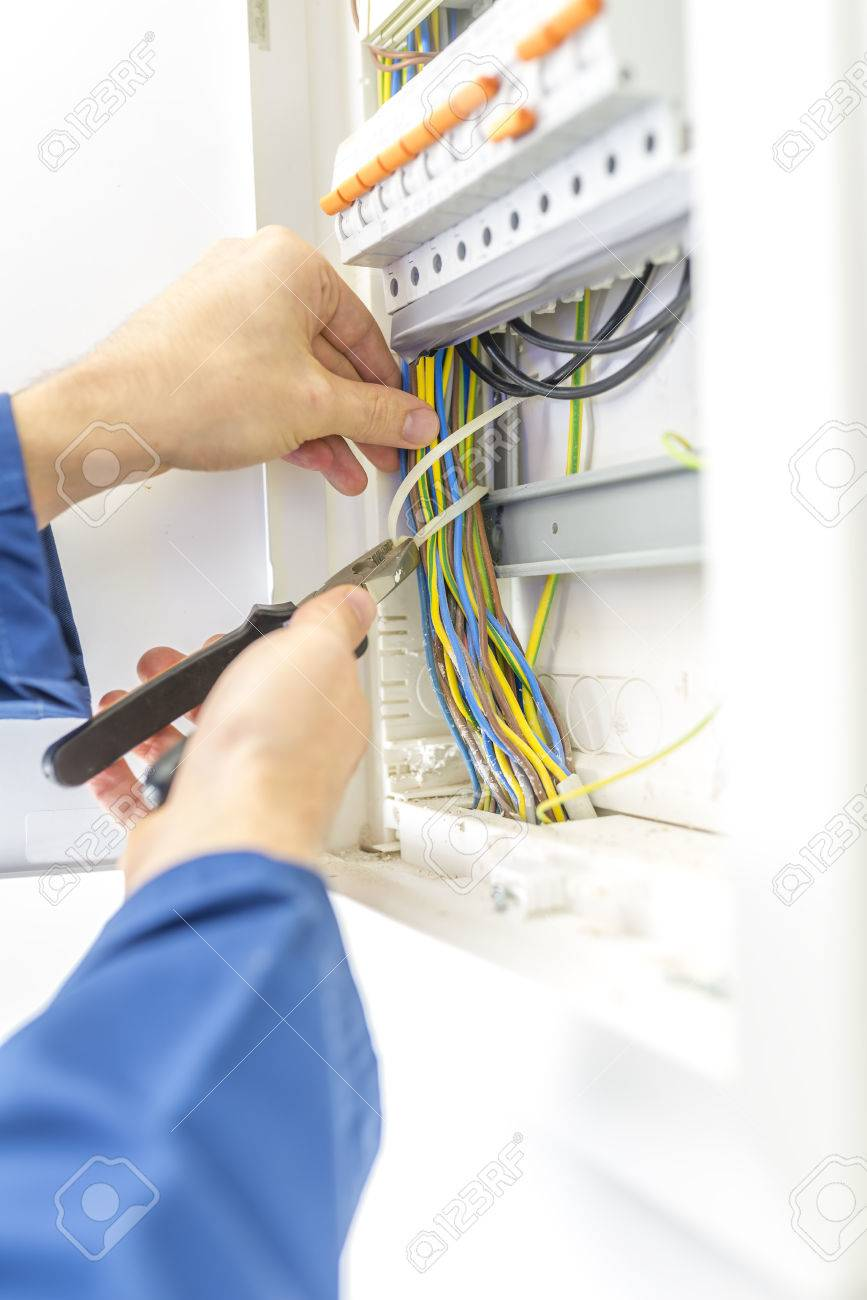 hight resolution of electrician checking the wiring in a fuse box providing the electrical supply to a domestic residence