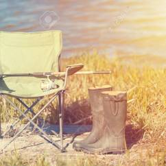 Green Fishing Chair Folding Beach Chairs Concept On Grass With Boots And Stock Spinning Rod Near Lake