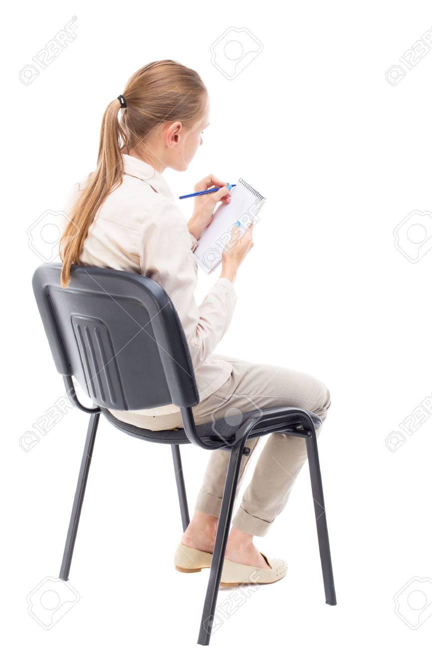 vue de dos de la belle jeune femme assise sur une chaise et prend des notes dans un carnet fille a regarder arriere collection vue de personnes