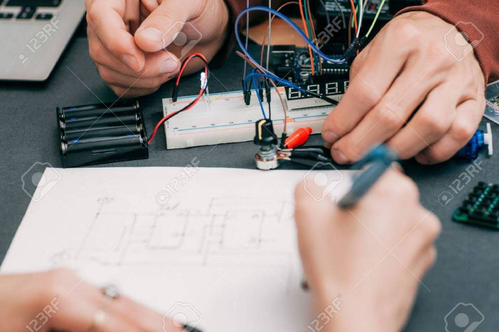 medium resolution of stock photo woman recapping electronics creation process engineer assistant drawing wiring diagram of electronic construction