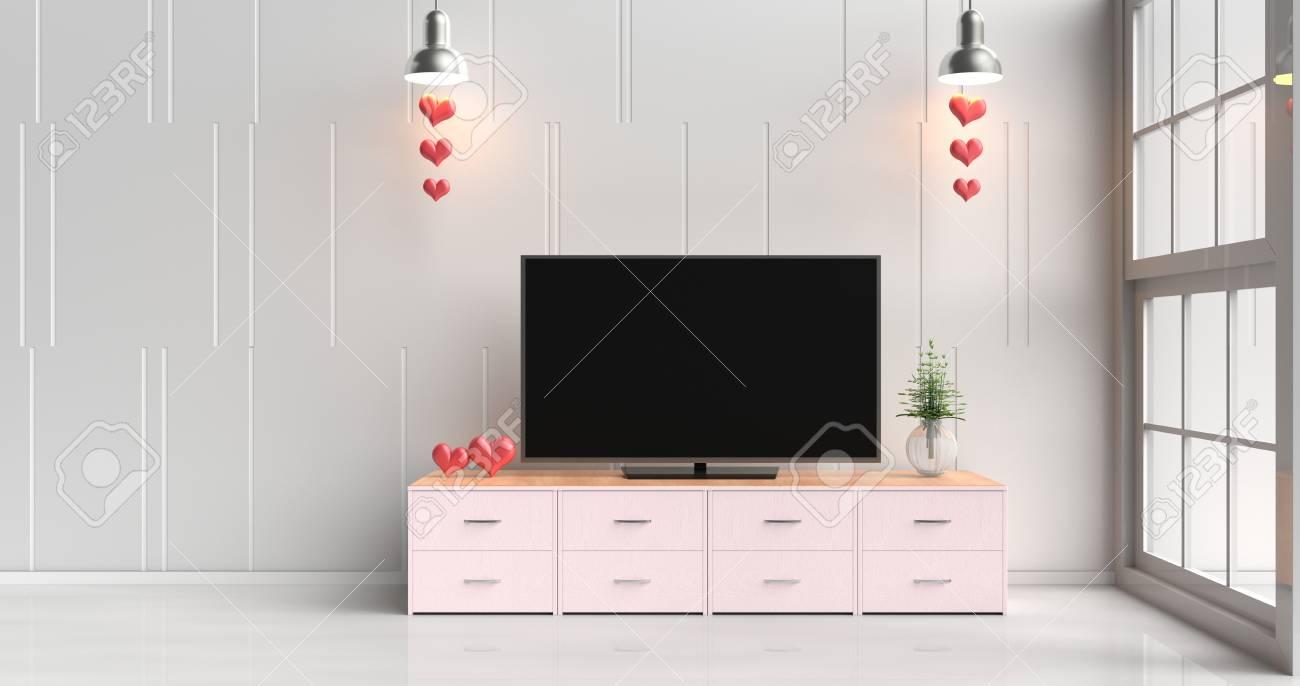 smart tv sur le support de television rose dans le salon blanc decore avec des coeurs rouges lampe bois rose meuble tv fenetre arbre dans un vase
