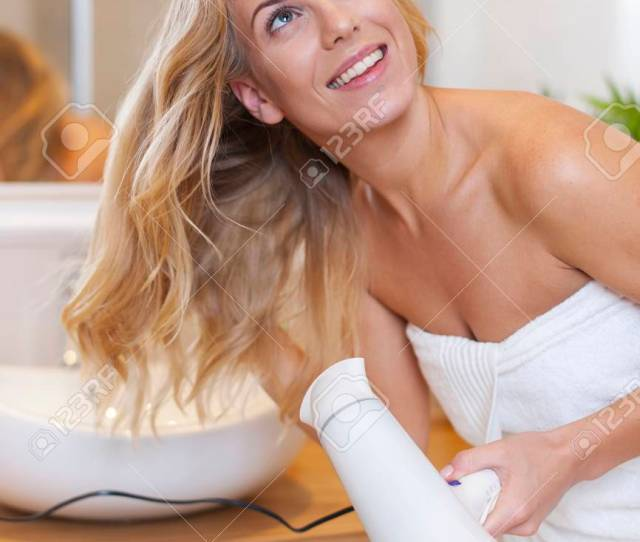 Blonde Woman Drying Hair After The Shower Stock Photo