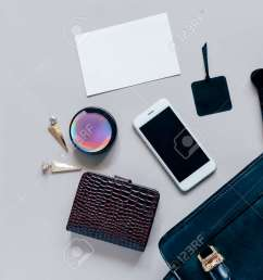 flat lay of black leather woman bag open out with cosmetics accessories wallet  [ 1300 x 927 Pixel ]