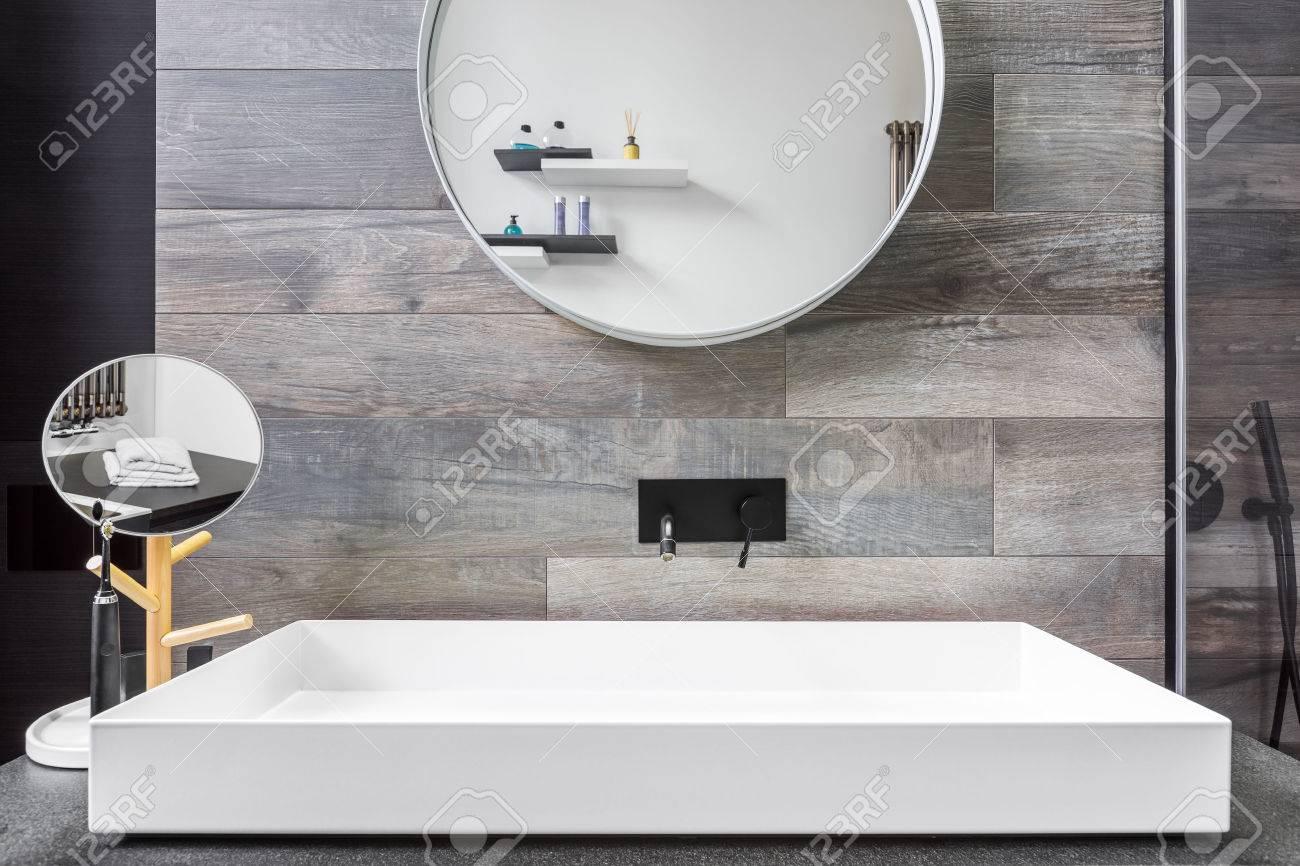 salle de bain avec lavabo a poser miroir et carrelage gris