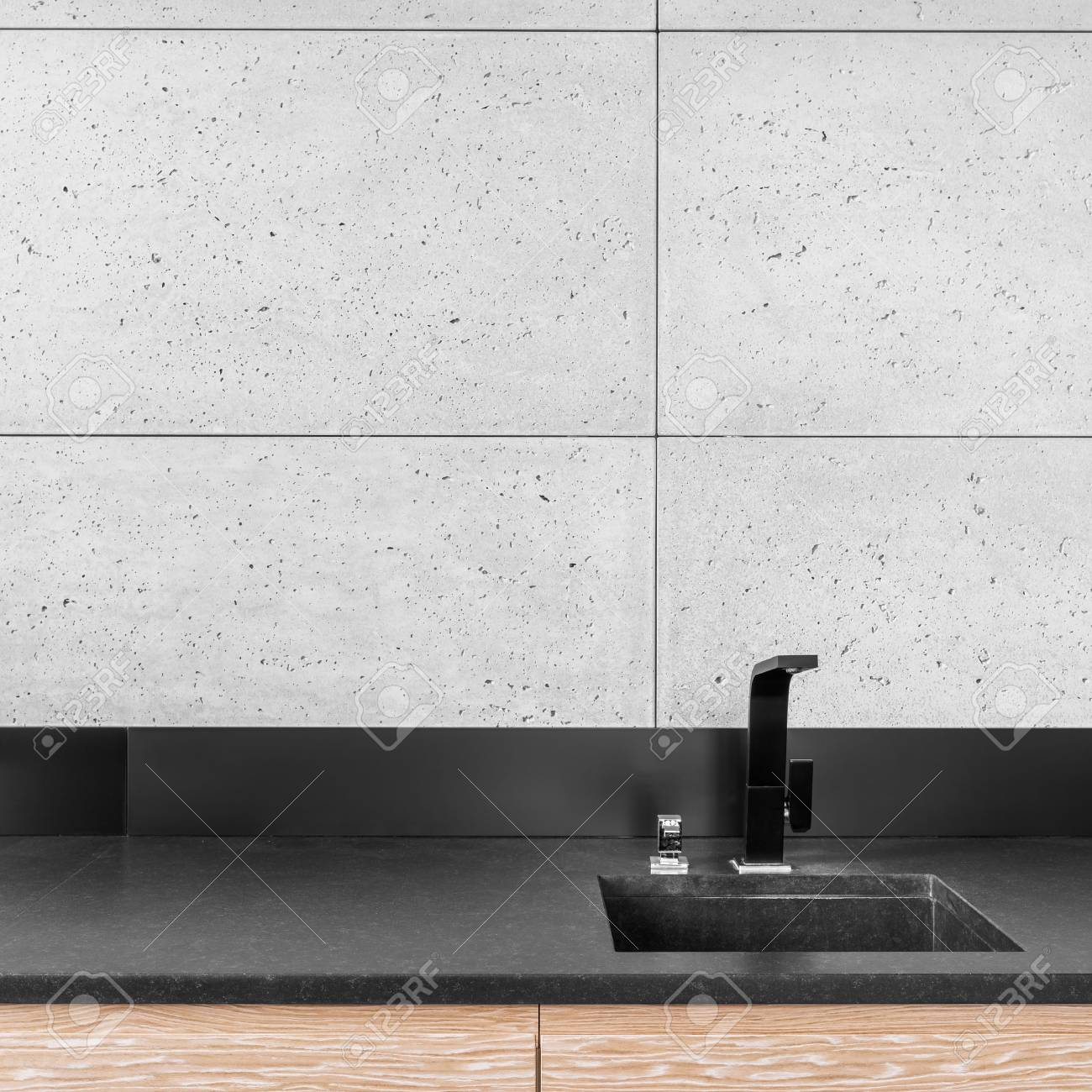 cuisine moderne avec carrelage mural gris plan de travail noir evier et robinet