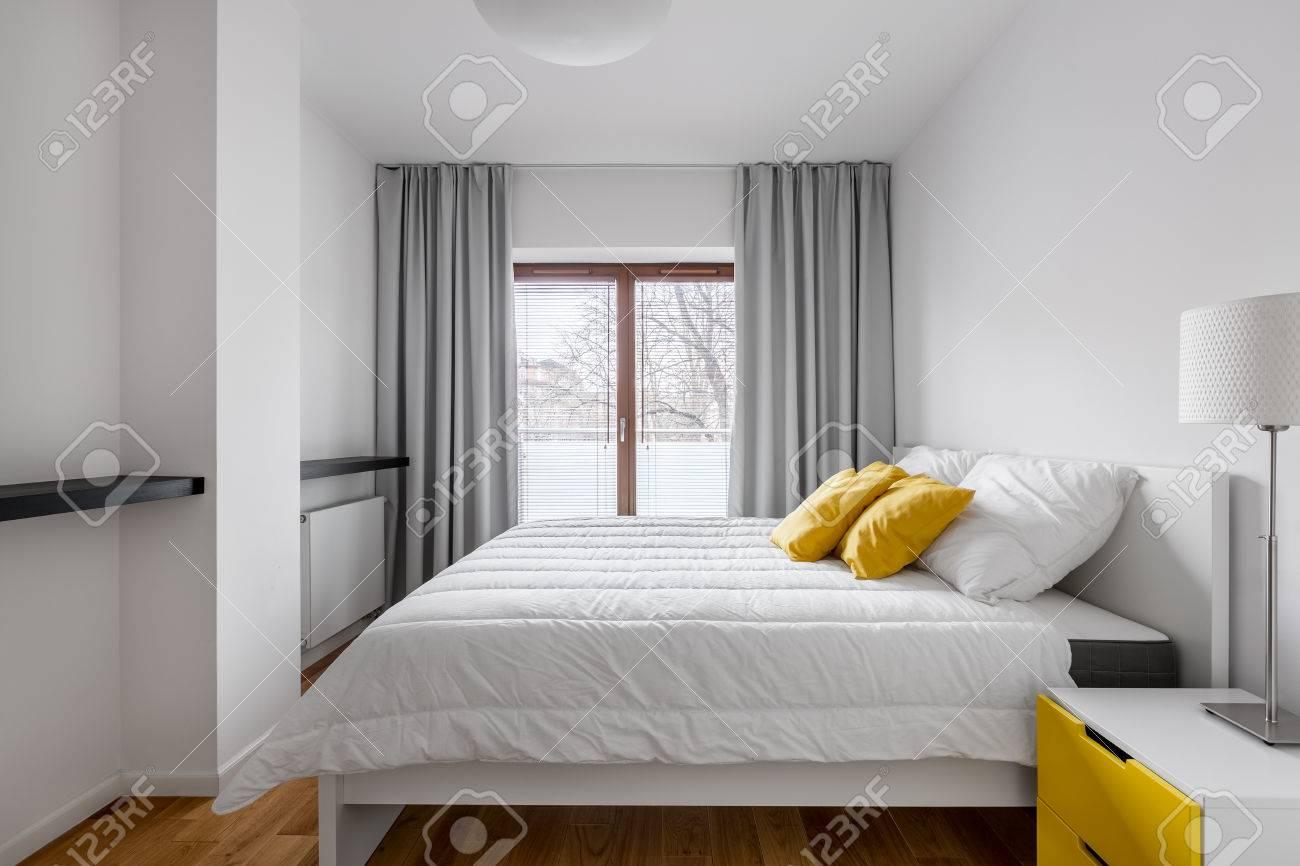 chambre blanche avec lit double fenetre rideaux gris lampe et table d appoint banque d images et photos libres de droits image 79389564