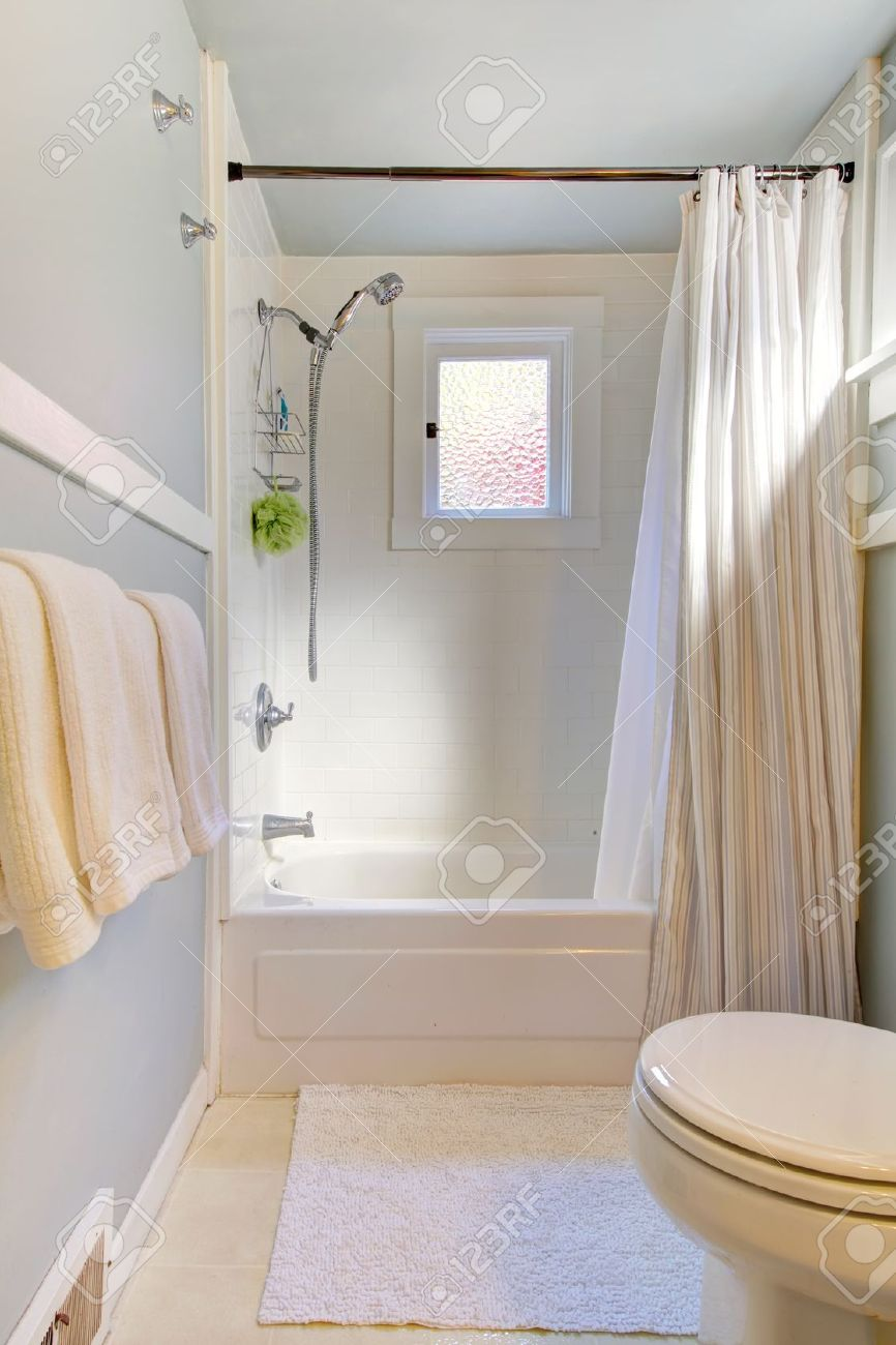 small blue bathroom with light grey blue and shower curtain
