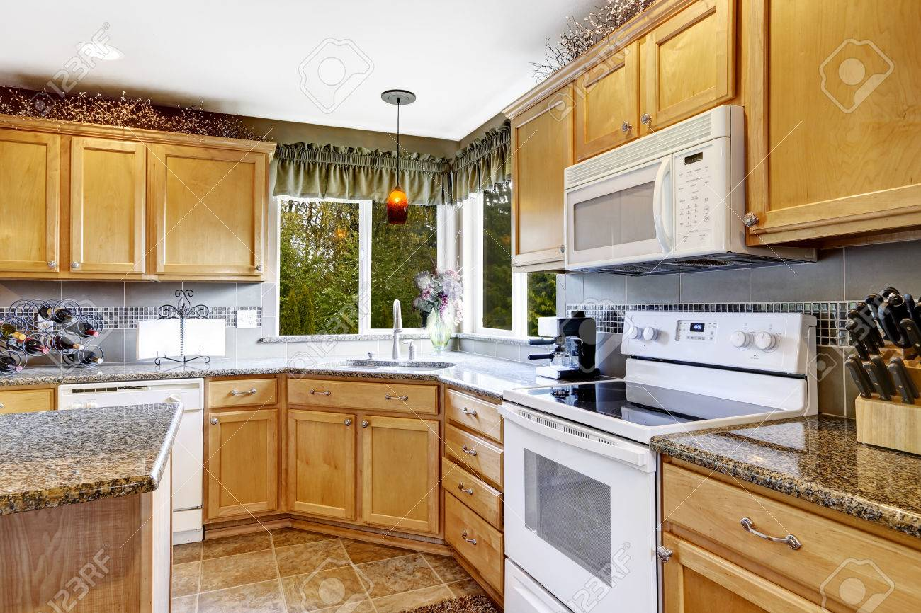 lumineuse salle de cuisine interieur avec carrelage au sol armoires de rangement brun clair et appareils blancs banque d images et photos libres de droits image 30094717