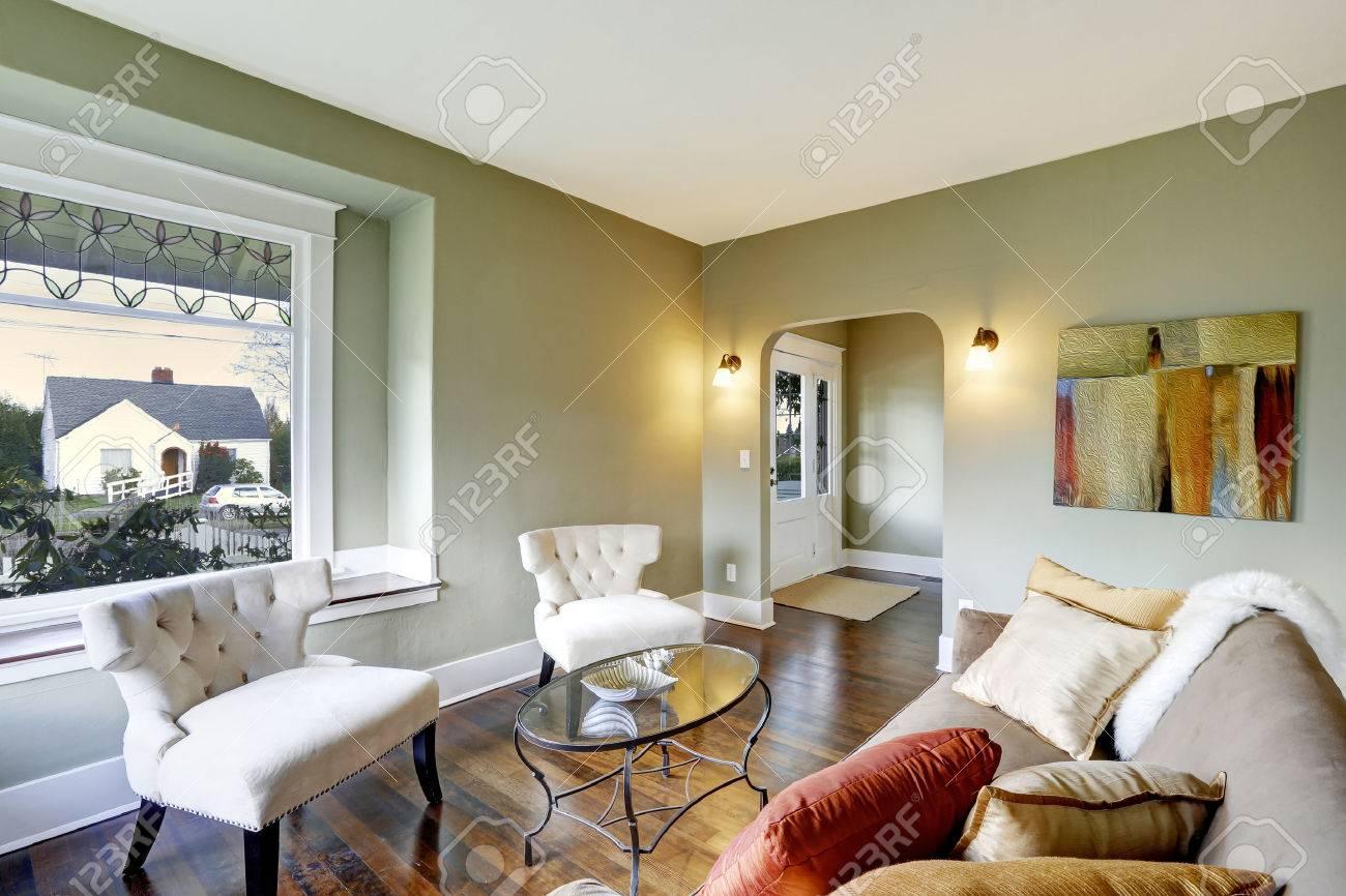 petit salon avec deux chaises classiques verre table basse et canape marron avec des coussins et tapis de fourrure